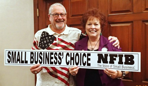 "Photographed holding one of NFIB's signature ""Small Business' Choice"" campaign sign-toppers, NFIB/Arizona Leadership Council Chairman Mark Giebelhaus congratulates former lawmaker Sylvia Tenney Allen after she was selected as replacement state senate nominee by Legislative District 6 Republicans at their August 30th special meeting in Flagstaff. The extraordinary selection became necessary when incumbent Sen. Chester Crandell died in an early-August horse-riding accident after primary ballots had already been sent to voters. Mr. Giebelhaus was on hand at the GOP meeting to inform Mrs. Allen that she would receive NFIB/Arizona SAFE Trust's endorsement. Mrs. Allen served in the Arizona Senate from 2008 to 2013 rising to the position of Senate President Pro Tempore in 2011. While in office, she achieved a perfect 100-percent score on NFIB/Arizona's Voting Records during her four-and-a-half years in the legislature."